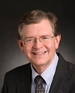 head shot of a man with glasses wearing a suit and tie