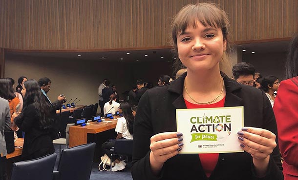 A smiling woman stands in a crowded room, with tables, chairs and other people visible in the background. She holds up a Climate Action for Peace sign.