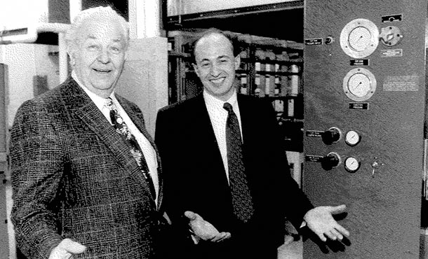 two men standing and smiling in front of lab equipment