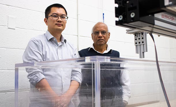 Two men stand in front of a tank of water in a research laboratory.