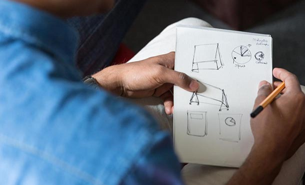 A man holds a piece of paper with rough design sketches on it.