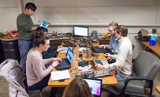 Six students sit with their laptops around a table, which is covered with wires and electronic components.