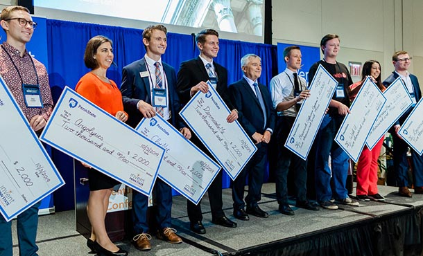 a line of students on a stage holding large presentation checks