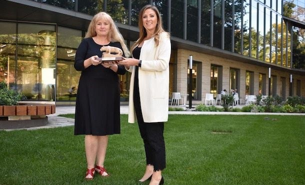 two women outside of a building holding an award