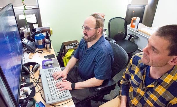 A man in a blue shirt with glasses and a man in a plaid shirt to his right work at a computer