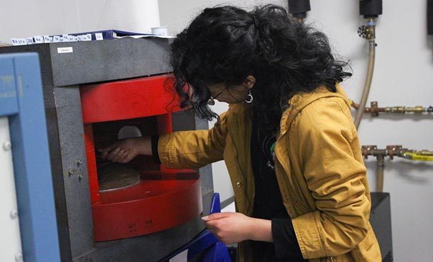A female high school student works with a piece of machinery in a lab.