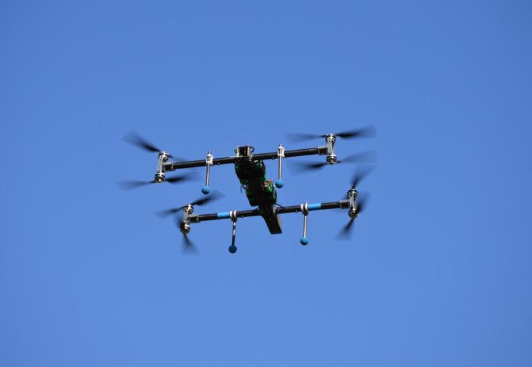 A small quadcopter flies against a blue sky.