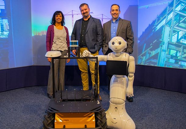 one woman and two men stand behind two medium-sized robots