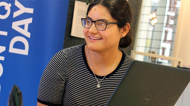 Hispanic female sitting behind the screen of a laptop computer smiling