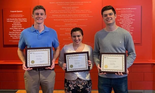 Three students, two male, one female, each holding framed Undergraduate Exhibition award in front of orange background.
