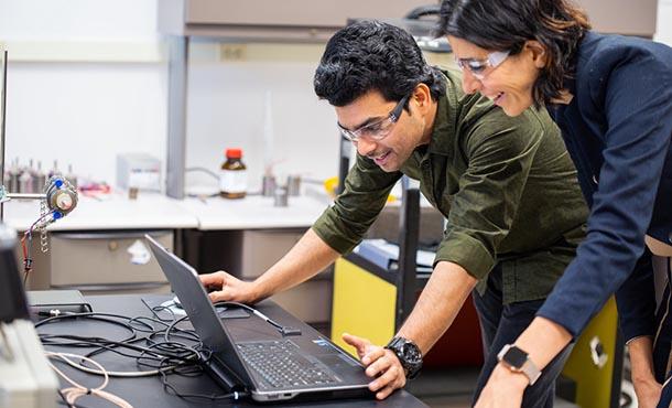 a man and woman look at a lap top computer screen