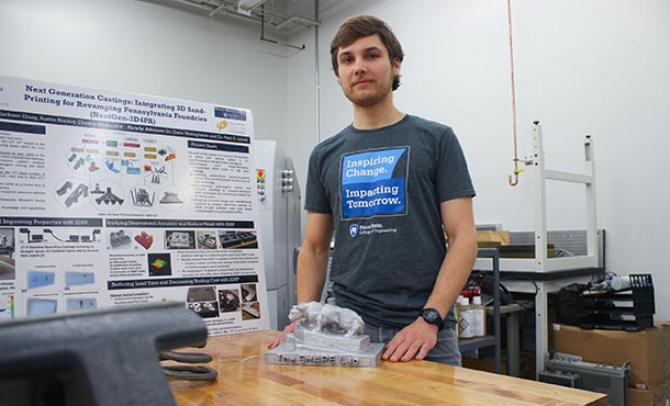 A man stands in an additive manufacturing lab with posters and equipment.