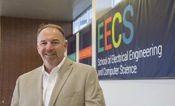 A man in a tan suit jacket poses in front of a School of E E C S wall banner