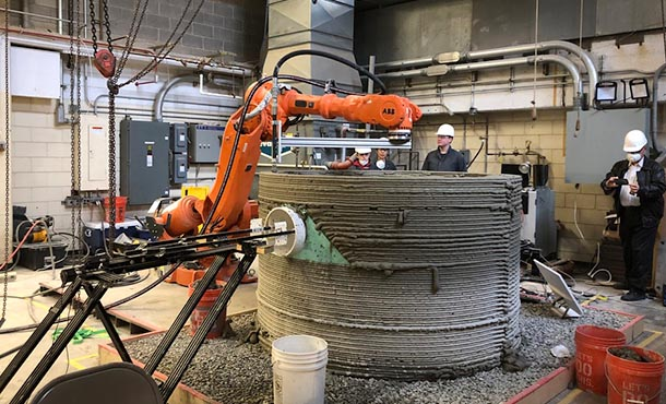 Four people look at an orange robotic arm as it moves above a cylinder concrete structure