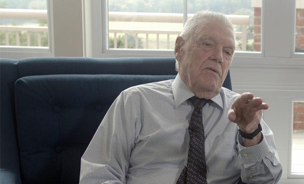 elderly man wearing a shirt and tie sitting in a chair speaking