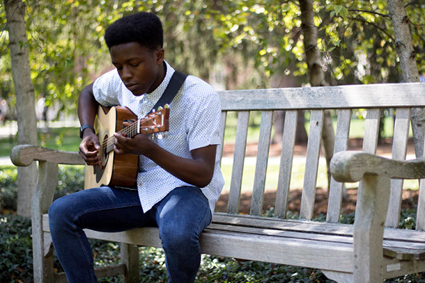 African American male playing a guitar