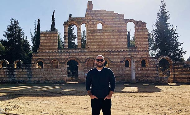 Joseph Najem stands in front of ruins.