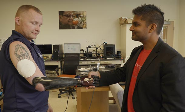 A man with a prosthetic right arm shakes hand with another man