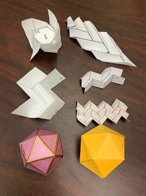 Seven origami paper structures are displayed on a brown table. Each structure is different.