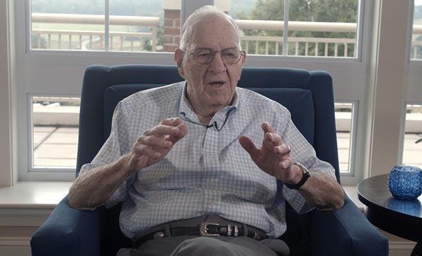 a man sitting in a chair, speaking to an interviewer
