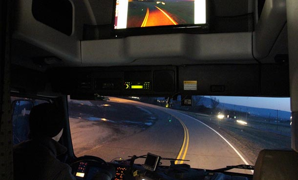 View of a marked roadway from inside a truck cabin with computer screens showing an image of the same road.