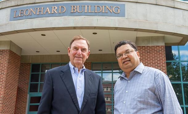 Two men in business attire stand before a building with a sign saying Leonhard Building.