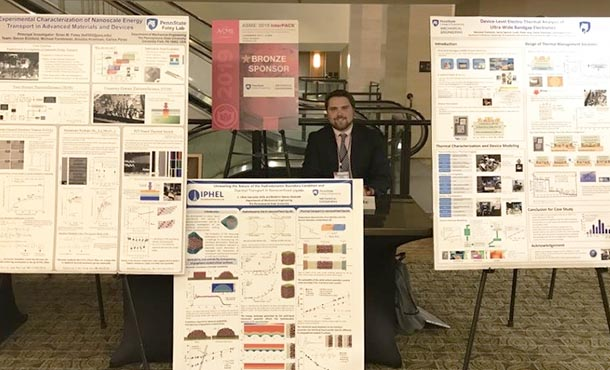 a man stands among several research posters
