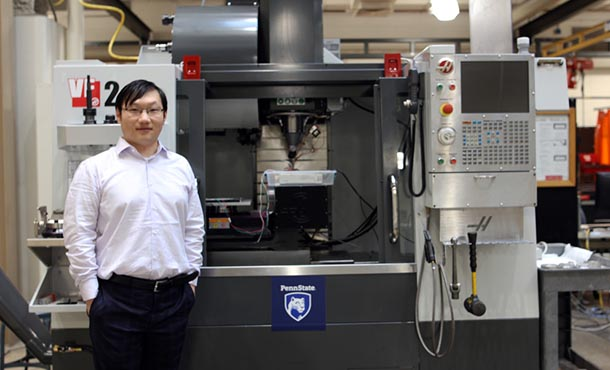 Hongtao Sun standing in front of a machine in the laboratory