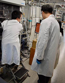 A man of short stature stands on a foot stool to work in a lab glove box while two others look on.