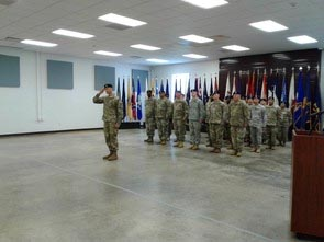 Saluting military man, dressed in uniform, stands in large room with group of soldiers in line behind him