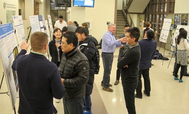 A group gathers in a large lobby area to view and discuss research posters