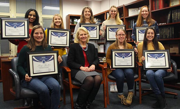 A group of undergraduate female students and a female administrator pose with certificates.