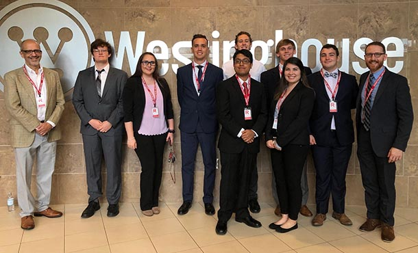 Ten people in business clothes stand in front of a silver sign that reads Westinghouse. They are all posed, looking at the camera.