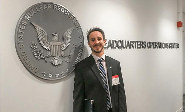 A man in a suit smiles and stands in front of a seal that reads Unites States Nuclear Regulatory Commission.