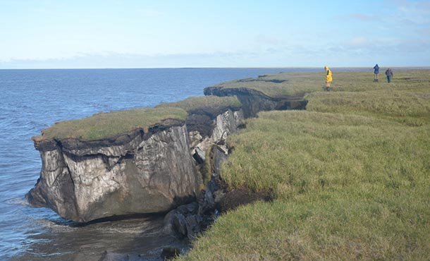 A large chunk of grassy land splits away from the coast, falling into the ocean.