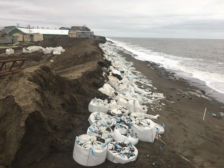 White bags line an eroded coastline, with buildings in the background. Ripped bags trail across the beach into the ocean.
