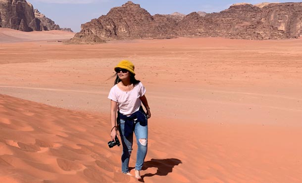 Young woman wearing sunglasses, a yellow hat, white t-shirt and jeans walks through the desert with a camera and stares off into the distance.
