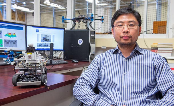Minghui Zhu sits at his desk. On the desk is a small device with wheels and wires, and behind him on the desk are two computer monitors and another small robot-like device.