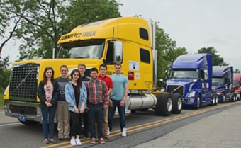 Students from the intelligent systems vehicle group stand in front of a truck platoon.