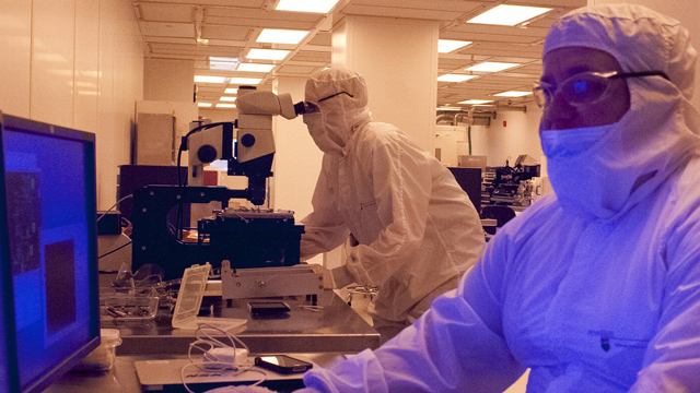 Two students in clean room gowns working in the NanoFabrication Lab